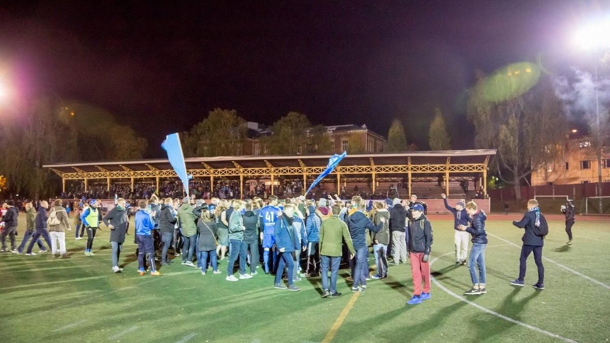 Kannattajat ja pelaajat juhlivat nousua kentällä