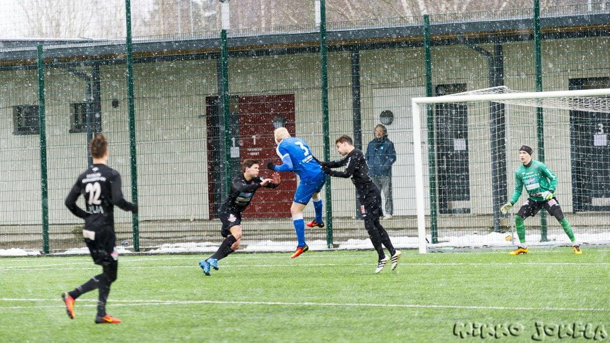 Roope Kostiainen taistelee pallosta lumisateen ja lahtelaiskäsien keskellä.